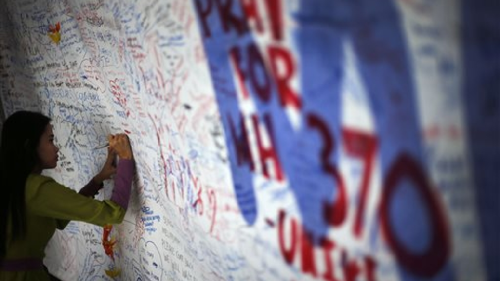 A woman writes on a board of messages and well-wishes dedicated to people involved with the missing Malaysia Airlines jetliner MH370, Saturday, March 15, 2014 in Sepang, Malaysia. The Malaysian passenger jet missing for more than a week had its communications deliberately disabled and its last signal came about seven and a half hours after takeoff, meaning it could have ended up as far as Kazakhstan or deep in the southern Indian Ocean, Malaysia's Prime Minister Najib Razak said Saturday. (AP Photo/Wong Maye-E)