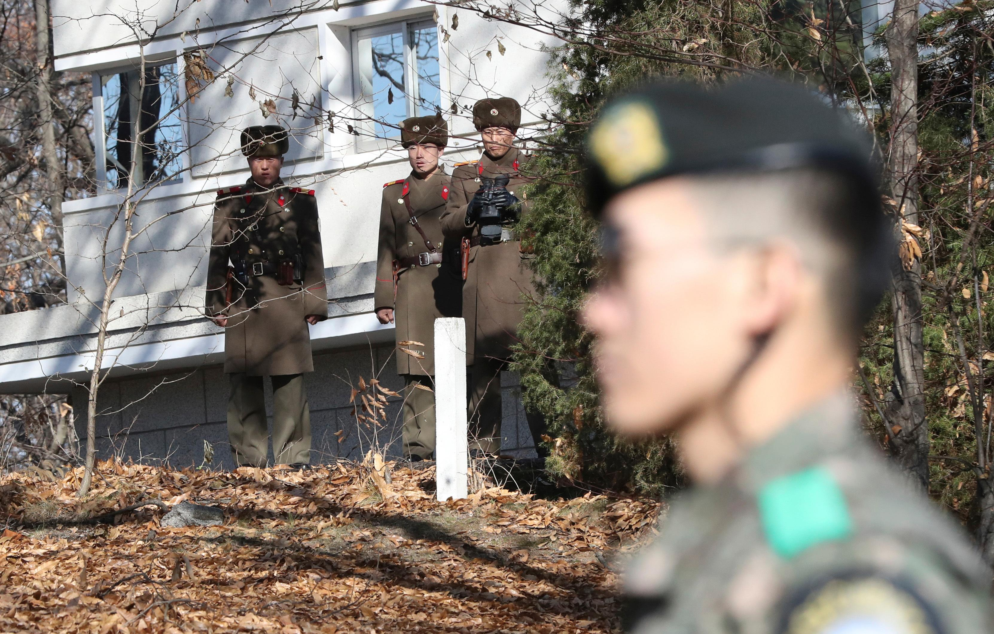 FILE - In this Nov. 27, 2017, file photo, North Korean soldiers look at the South side as a South Korean stands guard near the spot where a North Korean soldier crossed the border on Nov. 13 at the Panmunjom, in the Demilitarized Zone, South Korea. South Korea says on Thursday, Dec. 21, 2017, it has fired 20 rounds of warning shots as North Korean soldiers approached a military demarcation line at the border after their comrade defected to South Korea. (AP Photo/Lee Jin-man, File)