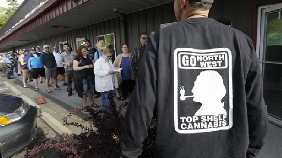 John Evich, right, an investor in the Top Shelf Cannabis store, talks to customers waiting in line outside the store, Tuesday, July 8, 2014, in Bellingham, Wash., on the first day of legal recreational marijuana sales in the state. (AP Photo/Ted S. Warren)