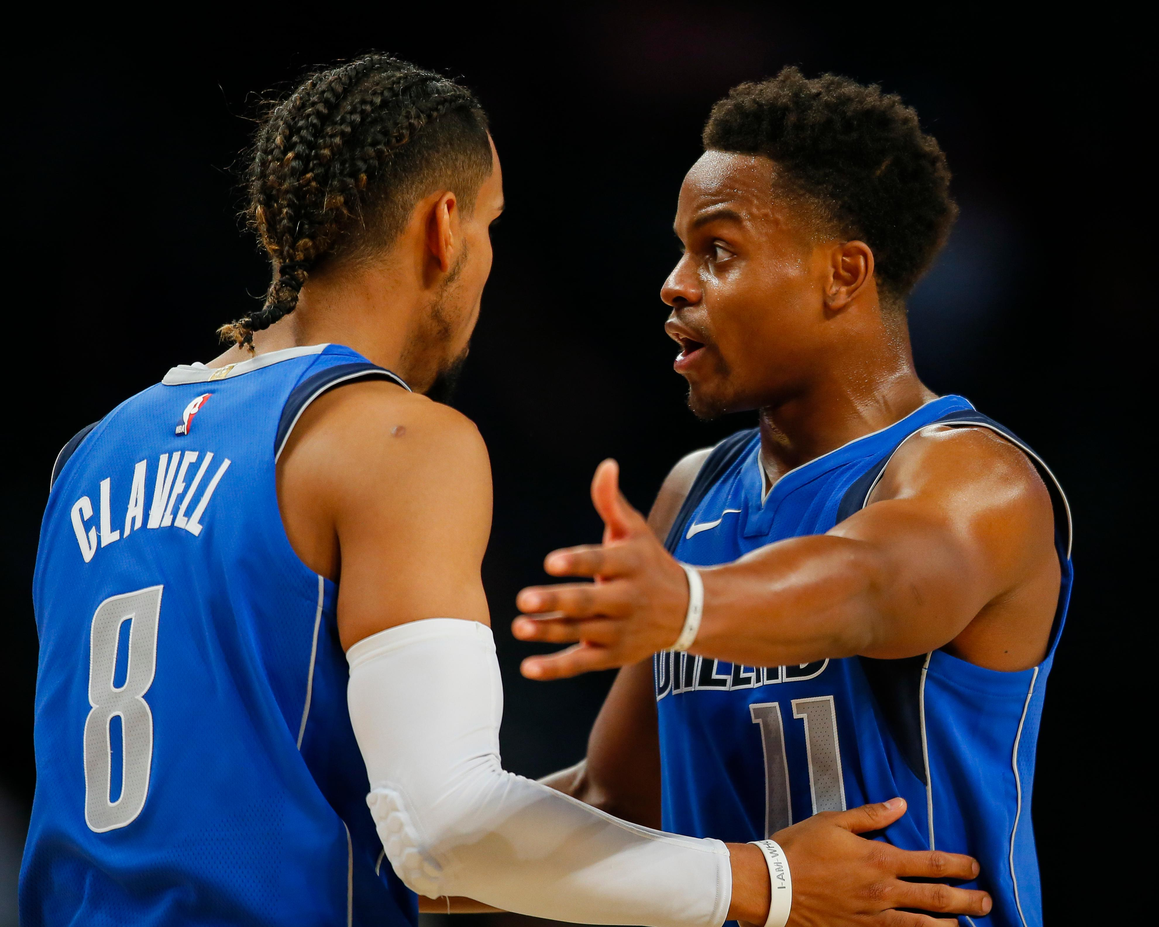 Dallas Mavericks guards Yogi Ferrell (11) and Gian Clavell (8) speak in the first half of an NBA preseason basketball game against the Atlanta Hawks, Thursday, Oct. 12, 2017, in Atlanta. (AP Photo/Todd Kirkland)