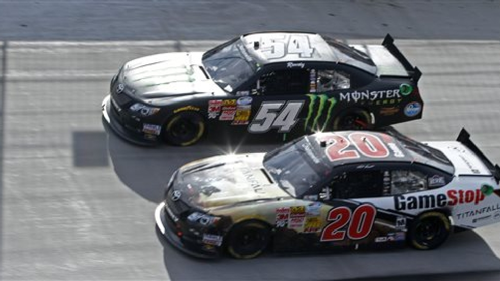 Kyle Busch (54) races with Matt Kenseth (20) during the NASCAR Nationwide Series auto race at Bristol Motor Speedway on Saturday, March 15, 2014, in Bristol, Tenn. Busch won the race. (AP Photo/Wade Payne)