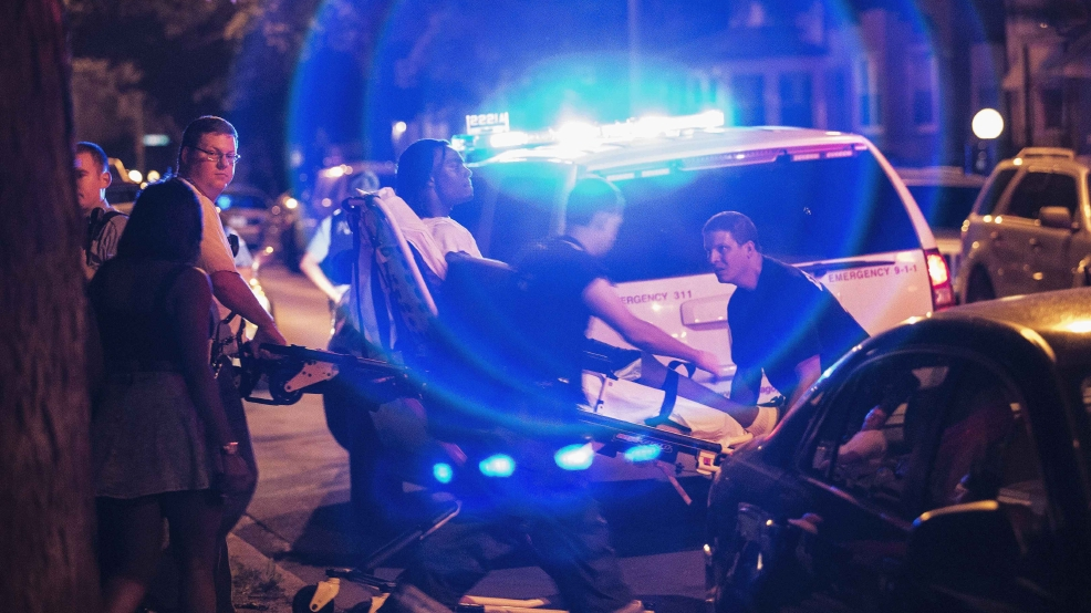 In this Sunday, July 6, 2014 photo, a man is wheeled on a stretcher after being shot in the leg on Chicago's South Side. (AP Photo/Sun-Times Media, Alex Wroblewski)