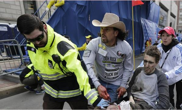 Medical workers carry injured man following explosion near Boston Marathon finish line.