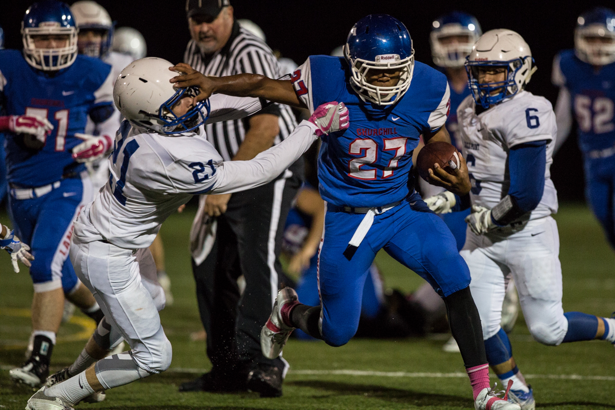Churchill Lancers running back Sam Jackson (#27) stiff arms Eagle Point safety Lucas Wilson (#21). Eagle Point defeated Churchill 42-37.  Photo by Austin Hicks, Oregon News Lab