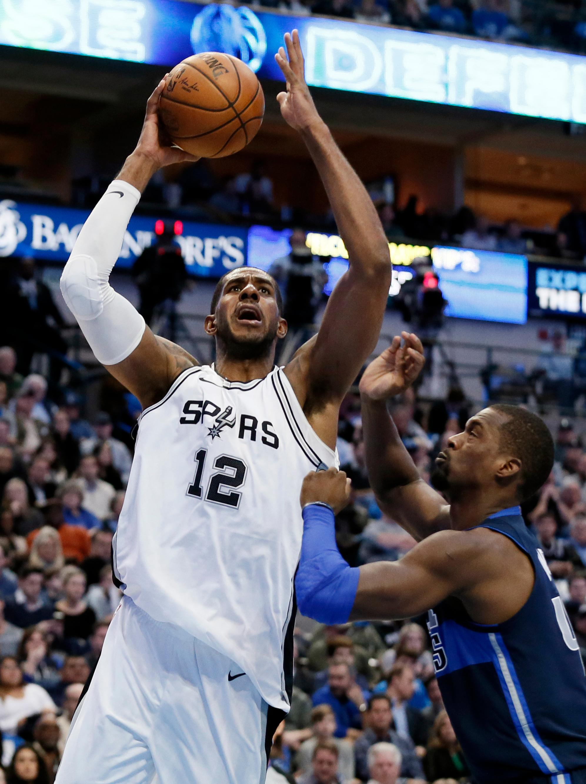 San Antonio Spurs forward LaMarcus Aldridge (12) goes up for a shot over Dallas Mavericks' Harrison Barnes (40) in the second half of an NBA basketball game, Tuesday, Dec. 12, 2017, in Dallas. The Mavericks won, 95-89. (AP Photo/Tony Gutierrez)