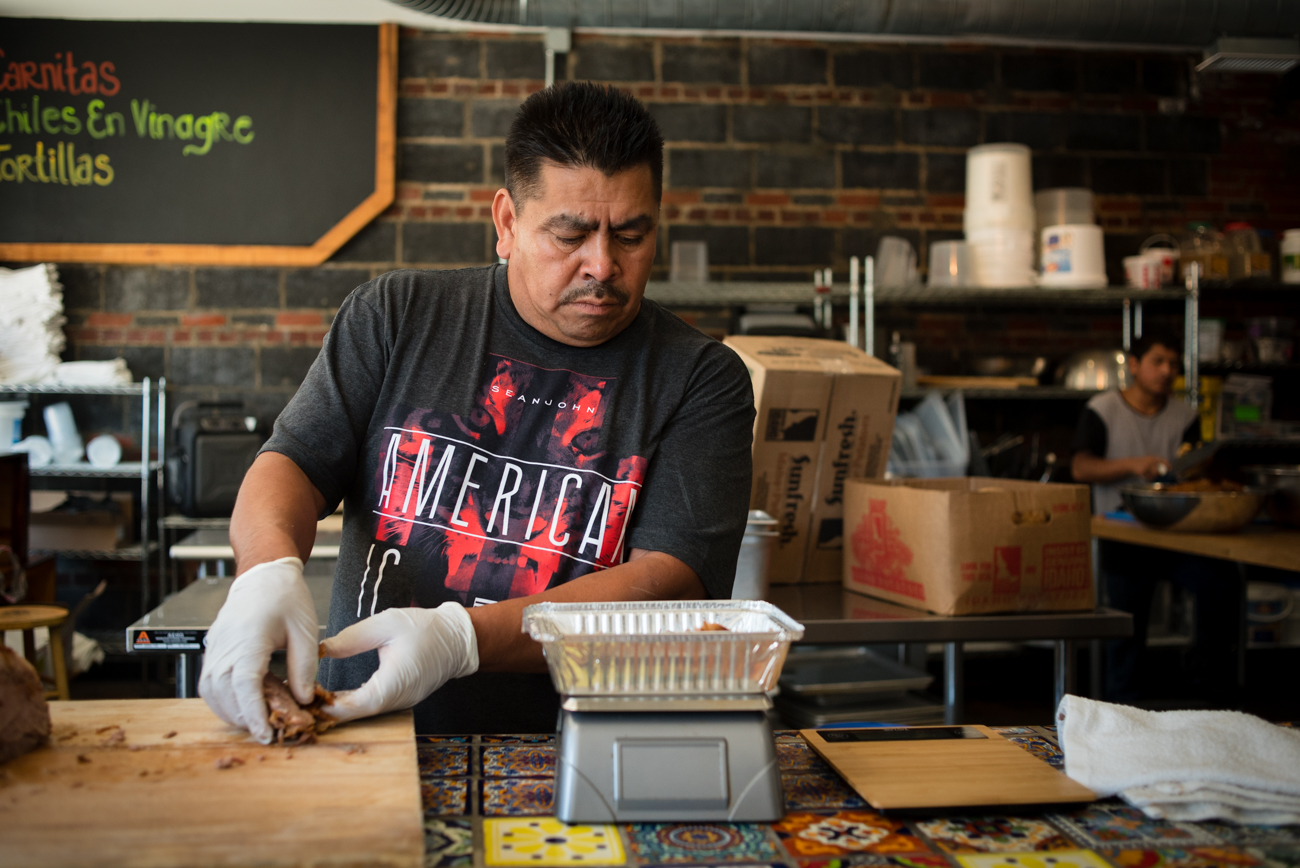 Kitchen manager Eduardo prepares a to-go order of carnitas. Eduardo has been with Mazunte since it first opened. / Image: Melissa Doss Sliney // Published: 7.4.17