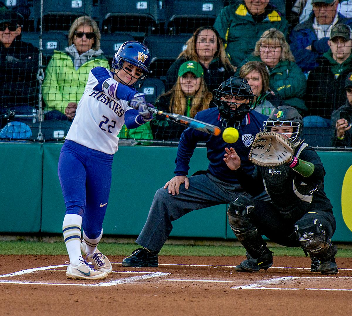 The Huskies' Sis Bates (#22) just barely misses the ball. In Game Two of a three-game series, the University of Oregon Ducks softball team defeated the University of Washington Huskies 4-1 Friday night in Jane Sanders Stadium. Danica Mercado (#2), Alexis Mack (#10) and Mia Camuso (#7) all scored in the win, Mack twice. The Ducks play the Huskies for the tie breaker on Saturday with the first pitch at noon. Photo by August Frank, Oregon News Lab