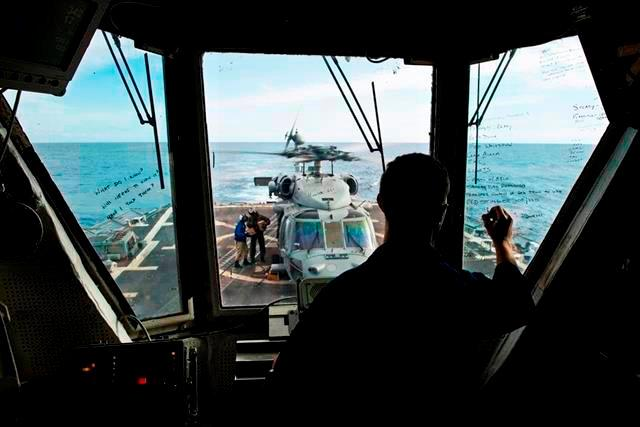U.S. Navy Ensign Robert Martinez tracks an SH-60S Seahawk helicopter from Helicopter Sea Combat Squadron 12 as it prepares to take off from the flight deck of the guided-missile destroyer USS Preble in the Coral Sea, July 22, 2013.