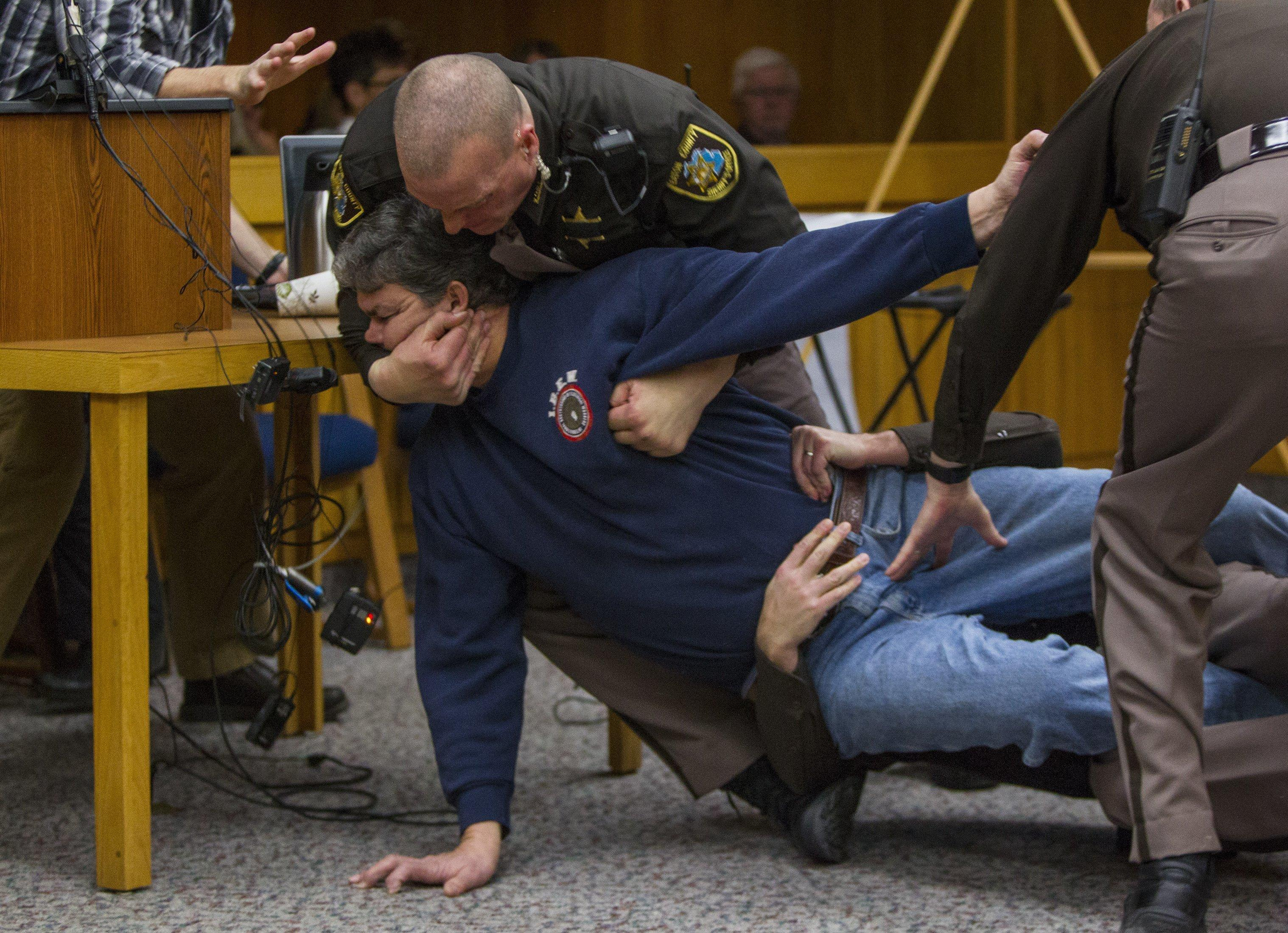 Eaton County Sheriff's deputies restrain Randall Margraves, father of three victims of Larry Nassar, Friday, Feb. 2, 2018, in Eaton County Circuit Court in Charlotte, Mich.  The incident came during the third and final sentencing hearing for Nassar on sexual abuse charges. The charges in this case focus on his work with Twistars, an elite Michigan gymnastics club.   (Cory Morse/The Grand Rapids Press via AP)