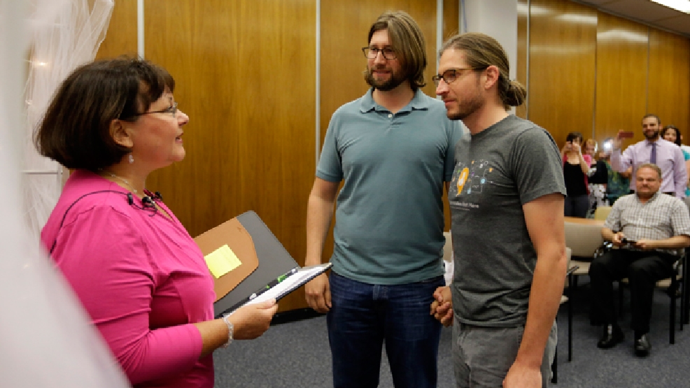 Jake Miller, right, 30, and Craig Bowen, 35, are married by Marion County Clerk Beth White, left, in Indianapolis, Wednesday, June 25, 2014. A federal judge struck down Indiana's ban on same-sex marriage Wednesday in a ruling that immediately allowed gay couples to wed. (AP Photo/Michael Conroy)