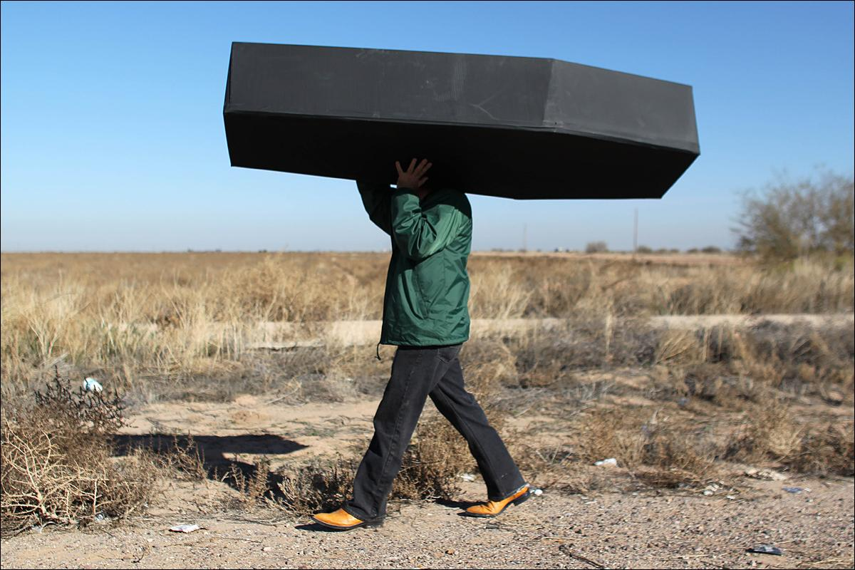 A demonstrator carries a mock coffin, representing migrants who have died inside a detention center in Eloy, Arizona, Wednesday, Jan. 20, 2016. Colombian musician Juanes and singer John Legend met immigrants at the detention center before performing for a small crowd outside the facility to draw attention to immigration. (AP Photo/Ricardo Arduengo)
