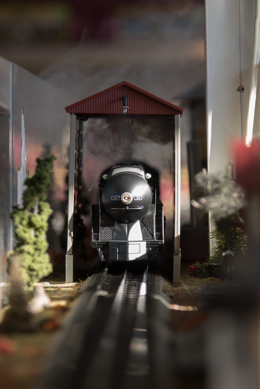 A model train charging through a tunnel while puffing vapor to simulate smoke. / Image: Phil Armstrong, Cincinnati Refined // Published: 2.27.20