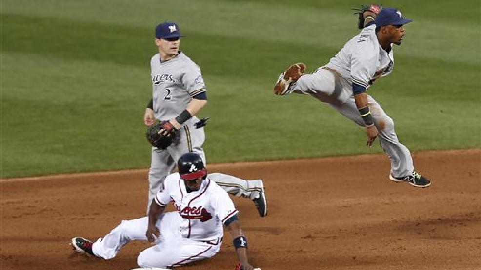 Milwaukee Brewers shortstop Jean Segura, right, leaps over Atlanta Braves' Justin Upton as he turns a double play on a Chris Johnson ground ball in the fourth inning of a baseball game Thursday, May 22, 2014 in Atlanta. Second baseman Scooter Gennett (2) looks on at left. (AP Photo/John Bazemore)