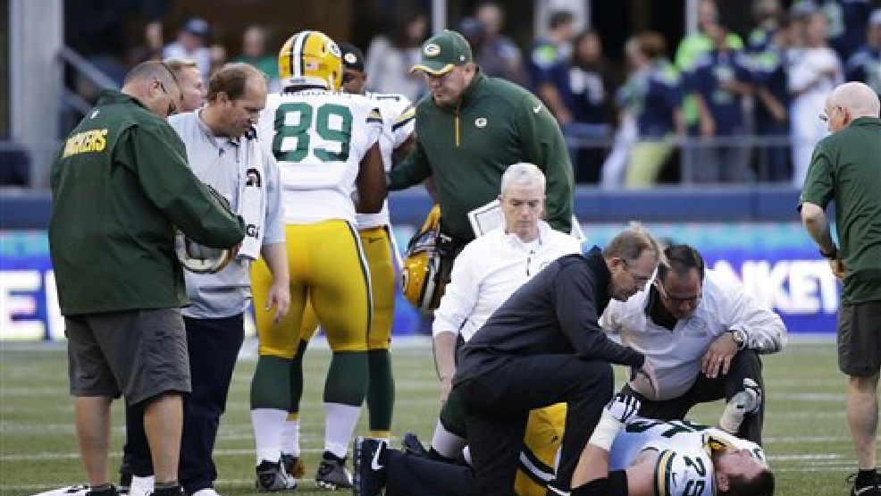 Green Bay Packers Bryan Bulaga (75) lies on the field with an injury during an NFL football game against the Seattle Seahawks, Thursday, Sept. 4, 2014, in Seattle. (AP Photo/Elaine Thompson)