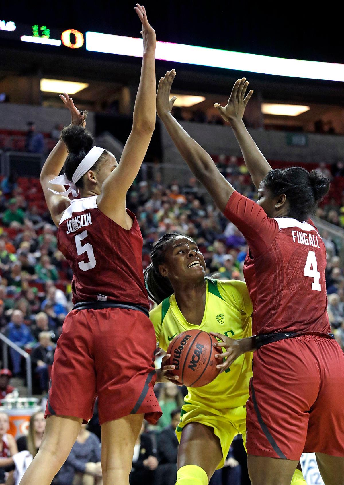Oregon's Ruthy Hebard, center, looks for room to move between Stanford's Kaylee Johnson (5) and Nadia Fingall (4) during the first half of an NCAA college basketball game in the finals of the Pac-12 Conference women's tournament, Sunday, March 4, 2018, in Seattle. (AP Photo/Elaine Thompson)