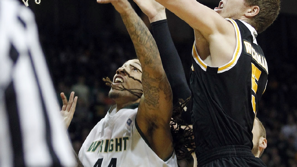 Milwaukee's Cody Whichmann, right, blocks a shot by Wright State's Tavares Sledge during the Horizon League men's tournament championship, Tuesday, March 11, 2014, in Dayton, Ohio. (AP Photo/The Dayton Daily News, Ty Greenlees)