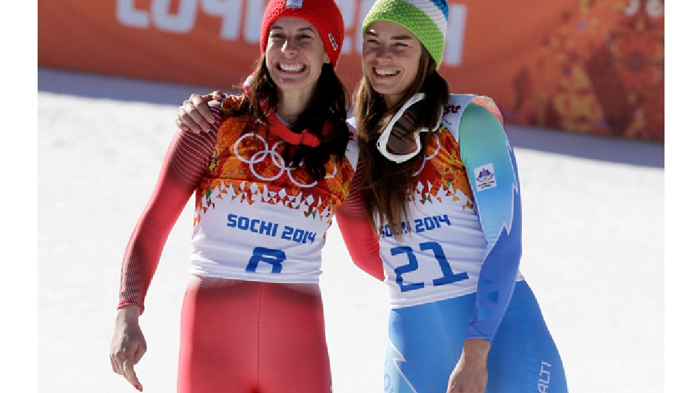 Women's downhill gold medal winners Switzerland's Dominique Gisin, left, and Slovenia's Tina Maze, right, pose for photographers on the podium during a flower ceremony at the Sochi 2014 Winter Olympics, Wednesday, Feb. 12, 2014, in Krasnaya Polyana, Russia. (AP Photo/Gero Breloer)