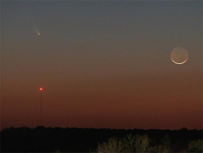 Comet Pan-STARRS is seen over the tower on the left as a 1 day waxing crescent Moon is seen setting in the Western sky on Tuesday, March 12, 2013.  The dark side of the Moon is lit by reflected light from the Earth, and is called Earthshine.  (AP Photo/Dr. Scott M. Lieberman)