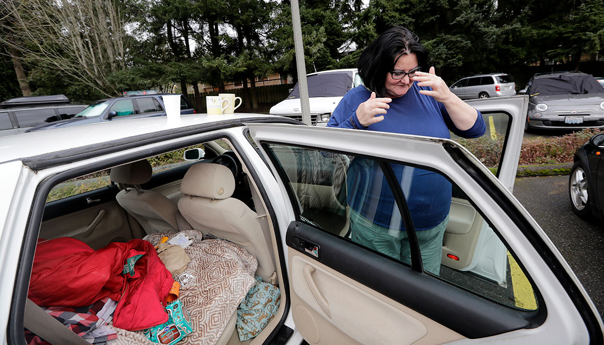 In this Monday, March 5, 2018, photo, Lisa Davis shows how she has her car set up to live in the church parking lot she shares with two-dozen or so other vehicles and their occupants, homeless single women, in Kirkland, Wash. Some of the obstacles faced by the women in finding permanent housing may soon become illegal in Washington state, where legislators are advancing a bill that would prohibit landlords from turning away tenants who rely on Section 8 vouchers, Social Security or veterans benefits. (AP Photo/Elaine Thompson)