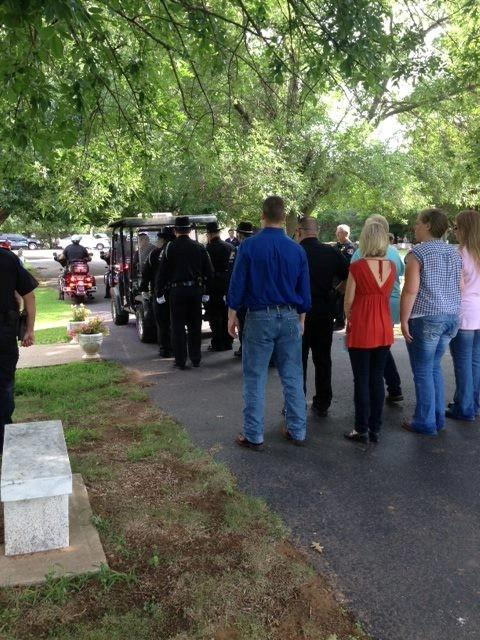 Mourners make their way through  Precious Pets Cemetery to Eron's gravesite.