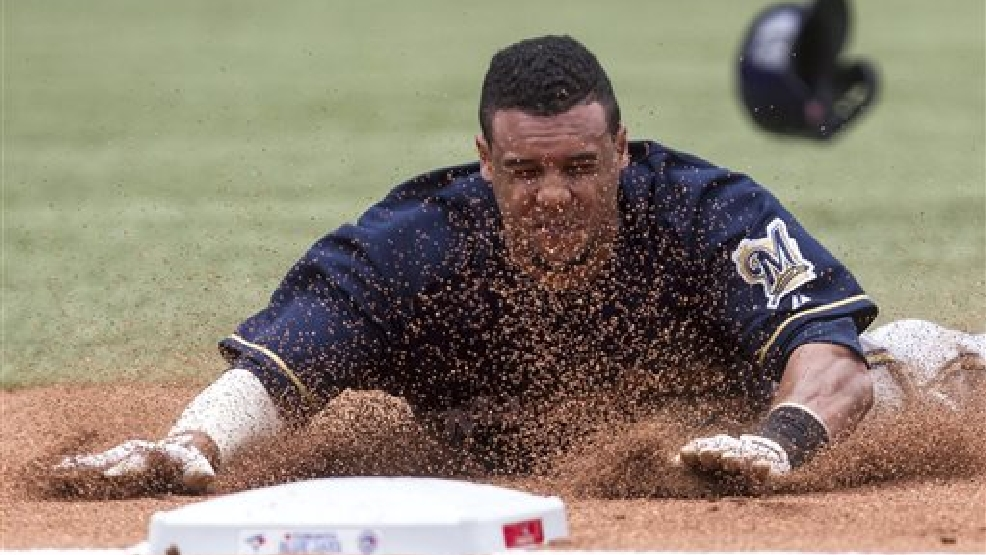 Milwaukee Brewers Carlos Gomez safely slides safely into third base after Aramis Ramirez grounded out to shortstop during seventh inning of a baseball game, Tuesday, July 1, 2014 in Toronto. (AP Photo/The Canadian Press, Chris Young)