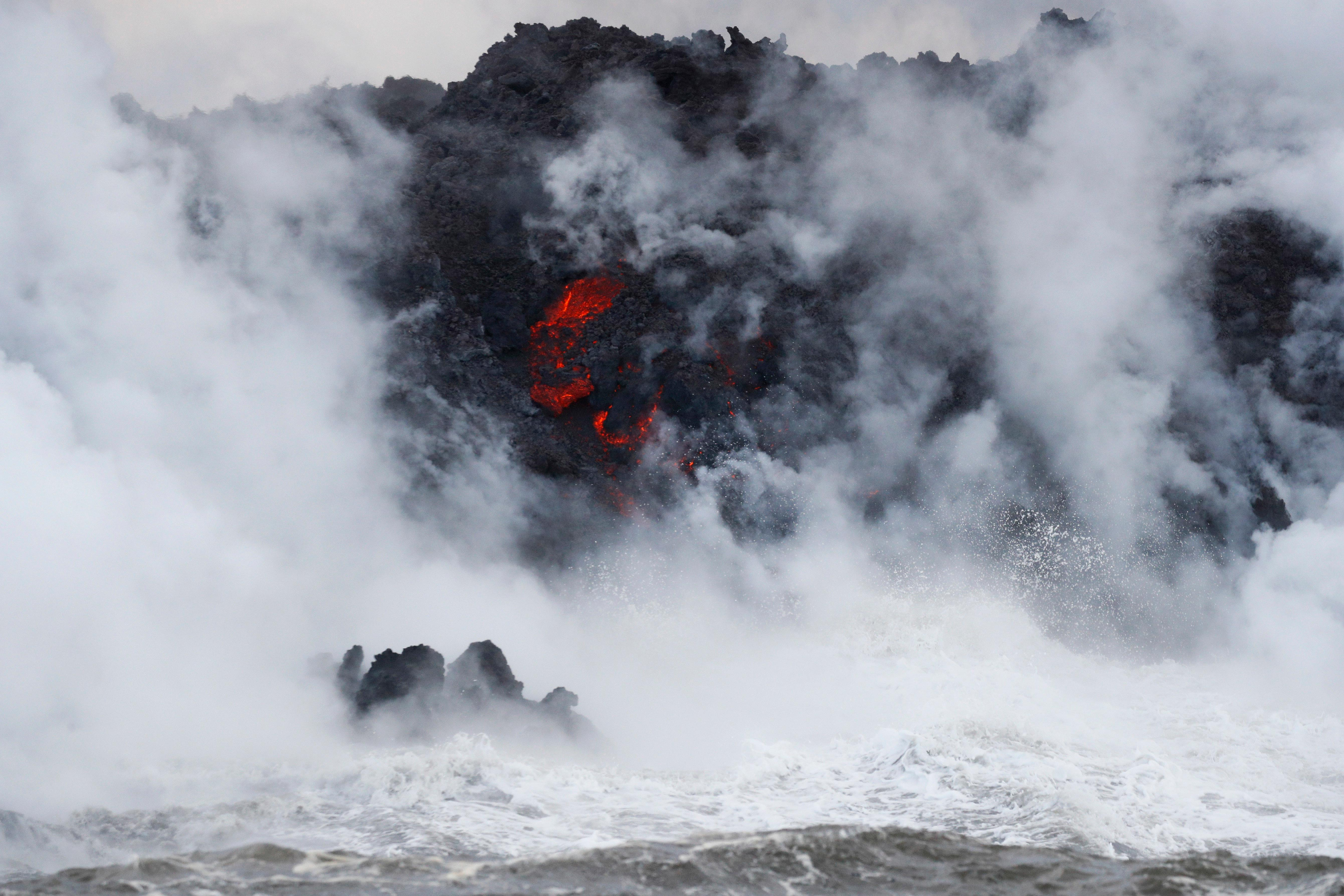 Steam rises as lava flows into the ocean near Pahoa, Hawaii, Sunday, May 20, 2018. Kilauea volcano that is oozing, spewing and exploding on Hawaii's Big Island has gotten more hazardous in recent days, with rivers of molten rock pouring into the ocean Sunday and flying lava causing the first major injury. (AP Photo/Jae C. Hong)