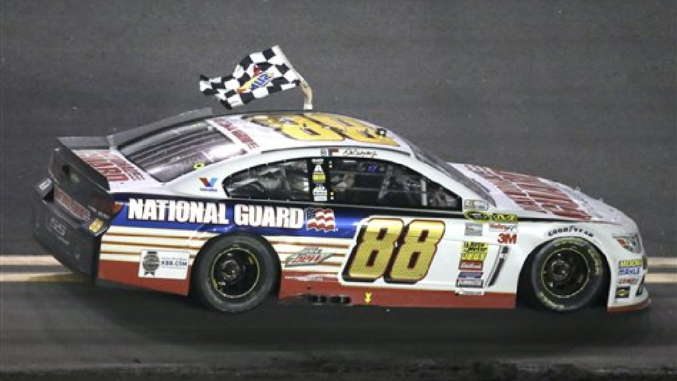 Dale Earnhardt Jr. drives in front of fans in the grandstands waving the checkered flag after winning the Daytona 500 NASCAR Sprint Cup Series auto race at Daytona International Speedway in Daytona Beach, Fla., Sunday, Feb. 23, 2014. (AP Photo/John Raoux)