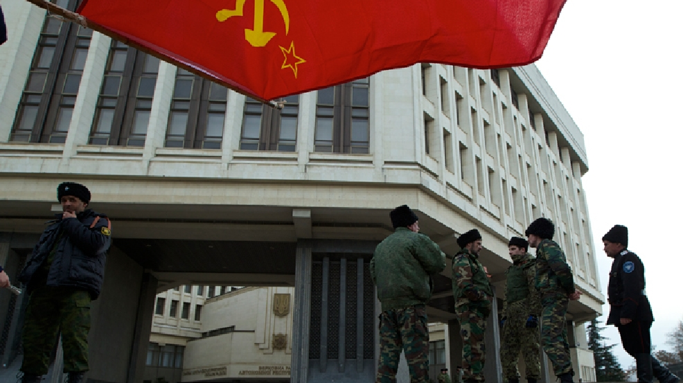 Soviet flag flies overhead as members of Cossack militia guard the local parliament building in Simferopol, Ukraine, on Thursday, March 6, 2014. (AP Photo/Ivan Sekretarev)