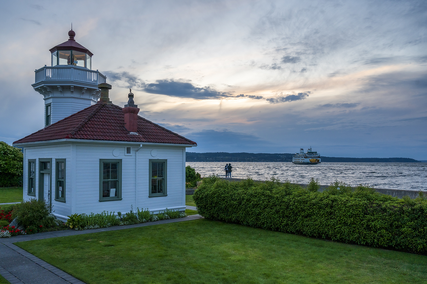 The sun sets on the Mukilteo Lighthouse as ferry traffic drifts by the small Victorian-style, operational light station, flashing a steady, navigational beam every five seconds. (Image: Rachael Jones / Seattle Refined)