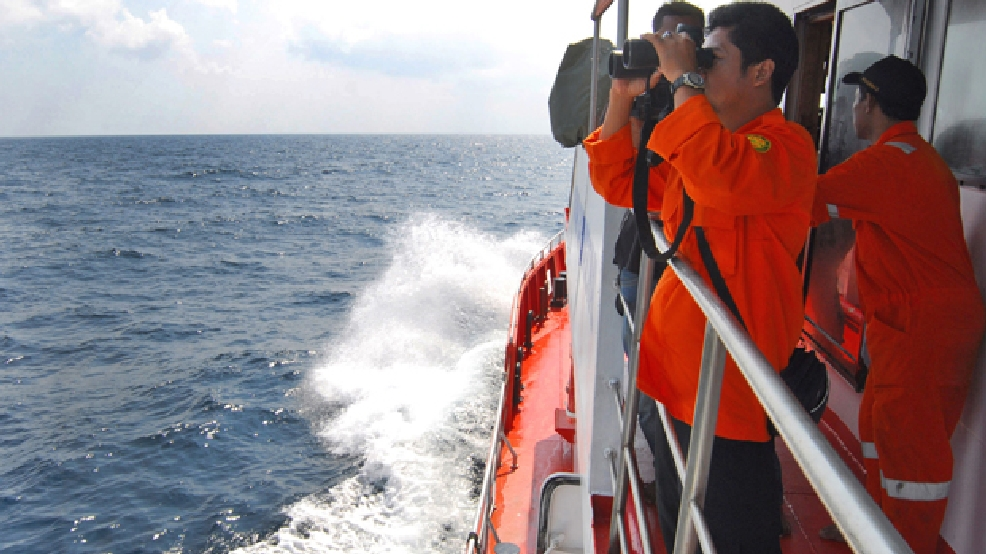 A member of Indonesian National Search and Rescue Agency (BASARNAS) uses a binocular to scan the horizon during a search operation for the missing Malaysia Airlines Boeing 777 conducted on the waters of the Strait of Malacca off Sumatra island, Indonesia, Wednesday, March 12, 2014. (AP Photo/Heri Juanda)
