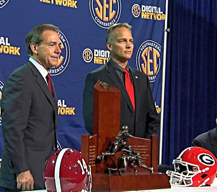 Nick Saban and Mark Richt pose for pictures with the SEC Championship football trophy.