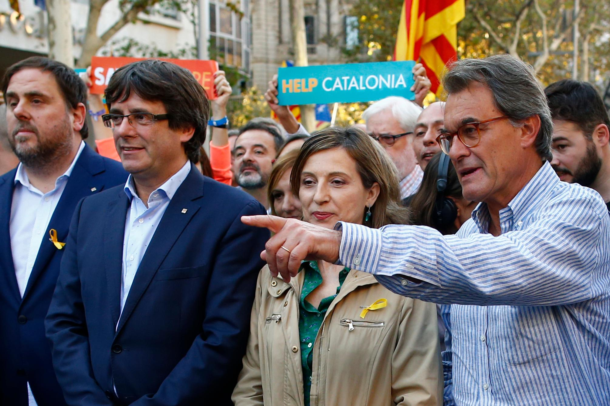 Former Catalan President Artur Mas, right, points next to Catalan deputy president Oriol Junqueras, left, President Carles Puigdemont, 2nd left and Carme Forcadell, speaker of the house in the Catalan parliament during a protest against the National Court's decision to imprison civil society leaders, in Barcelona, Spain, Saturday, Oct. 21, 2017. The Spanish government moved decisively Saturday to use a previously untapped constitutional power so it can take control of Catalonia and derail the independence movement led by separatist politicians in the prosperous industrial region. (AP Photo/Manu Fernandez)