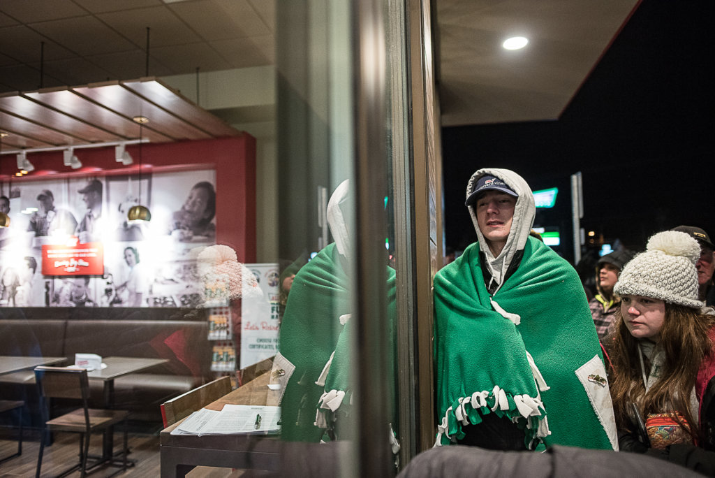 Ryan Pratt and Paige Maheux peer inside the Krispy Kreme store moments before the opening. The two waited outside in below freezing temperatures overnight for the grand opening of the store. (Andree Kehn/Sun Journal)