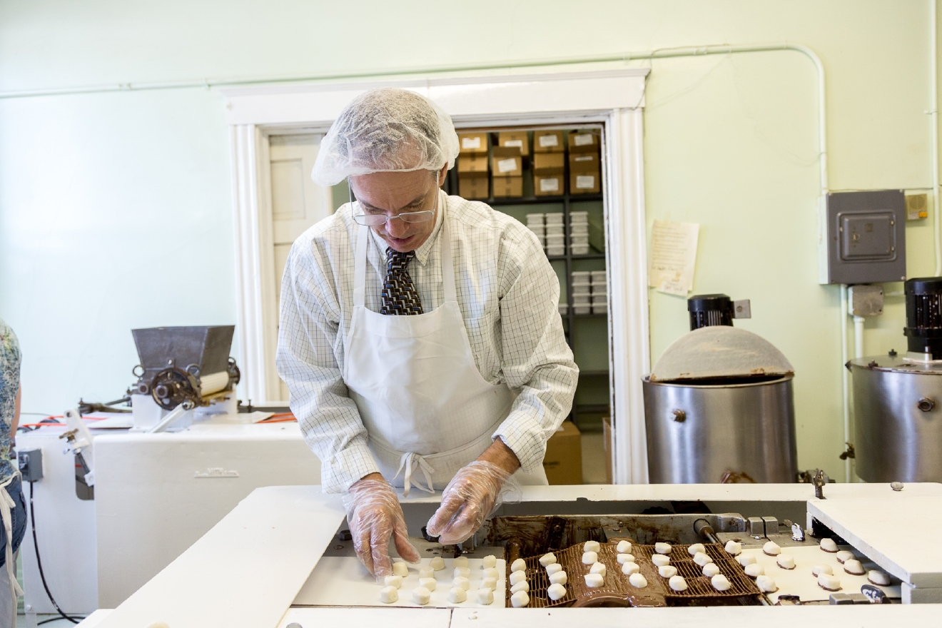 Some candies get a first dip of chocolate on the bottom before the final full dip. / Image: Daniel Smyth Photography
