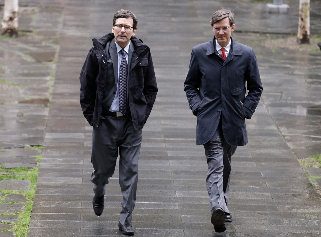 Attorney General Bob Ferguson, left, arrives at the federal courthouse with spokesman Peter Lavallee before an immigration hearing Wednesday, March 15, 2017, in Seattle. Washington state has filed a backup motion in an effort to keep President Donald Trump's revised travel ban from taking effect as scheduled Thursday. In a new court filing Wednesday, Ferguson said the state supports the arguments made in a related case filed by an immigrant rights group based in Seattle that alleges the ban discriminates against Muslims and violates federal immigration law. (AP Photo/Elaine Thompson)