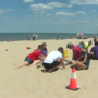 Teens help remove plastic beads from sand at Jean Klock Beach
