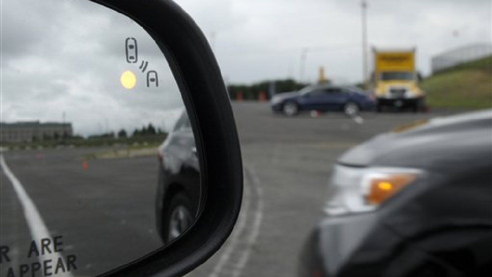 This May 22, 2012 file photo shows a demonstration of a side mirror warning signal in a Ford Taurus at an automobile testing area in Oxon Hill, Md. The Obama administration said Monday it is taking a first step toward requiring that future cars and light trucks be equipped with technology that enables them to warn each other of potential danger in time to avoid collisions. A research report released by the National Highway Traffic Safety Administration estimates that the technology could eventually prevent 592,000 left-turn and intersection crashes a year, saving 1,083 lives. The agency said it will begin drafting rules to require the technology in new vehicles. (AP Photo/Susan Walsh, File)