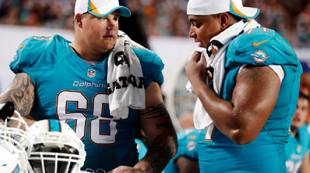 FILE - In this Aug. 24, 2013, file photo, Miami Dolphins guard Richie Incognito (68) and tackle Jonathan Martin (71) look over plays during an NFL preseason football game against the Tampa Bay Buccaneers in Miami Gardens, Fla. (AP Photo/Wilfredo Lee, File)