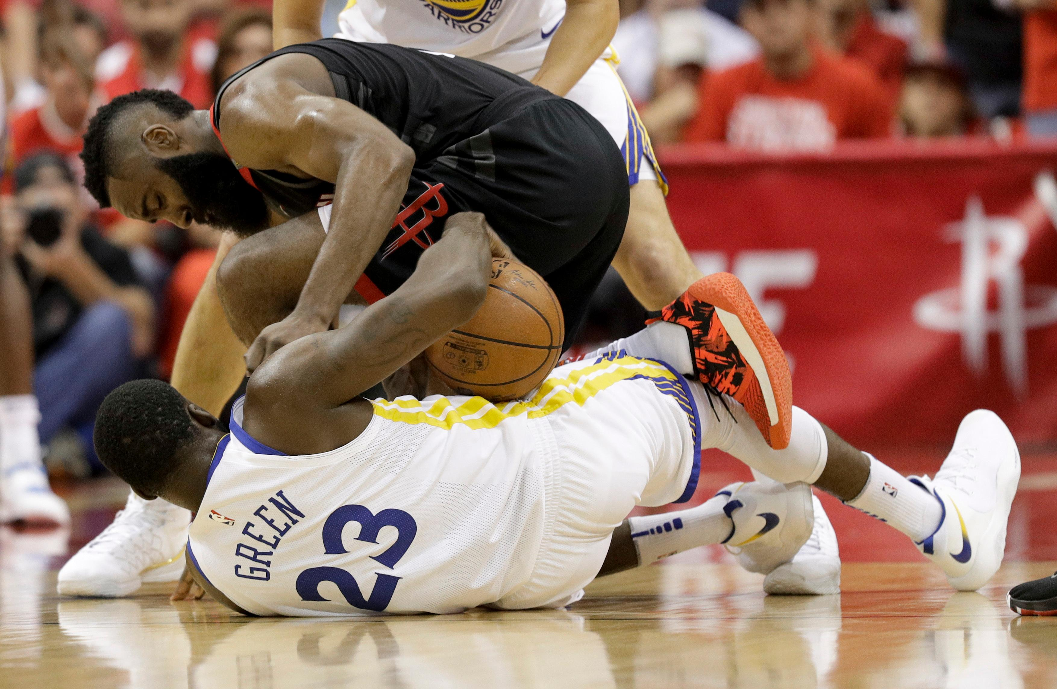 Houston Rockets guard James Harden, top, battles Golden State Warriors forward Draymond Green for a loose ball during the first half in Game 5 of the NBA basketball playoffsWestern Conference finals in Houston, Thursday, May 24, 2018. (AP Photo/David J. Phillip)