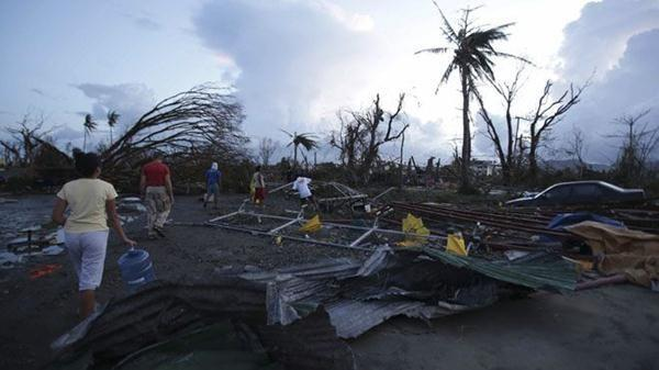 Residents walk by debris after powerful Typhoon Haiyan slammed into Tacloban city, Leyte province, central Philippines.