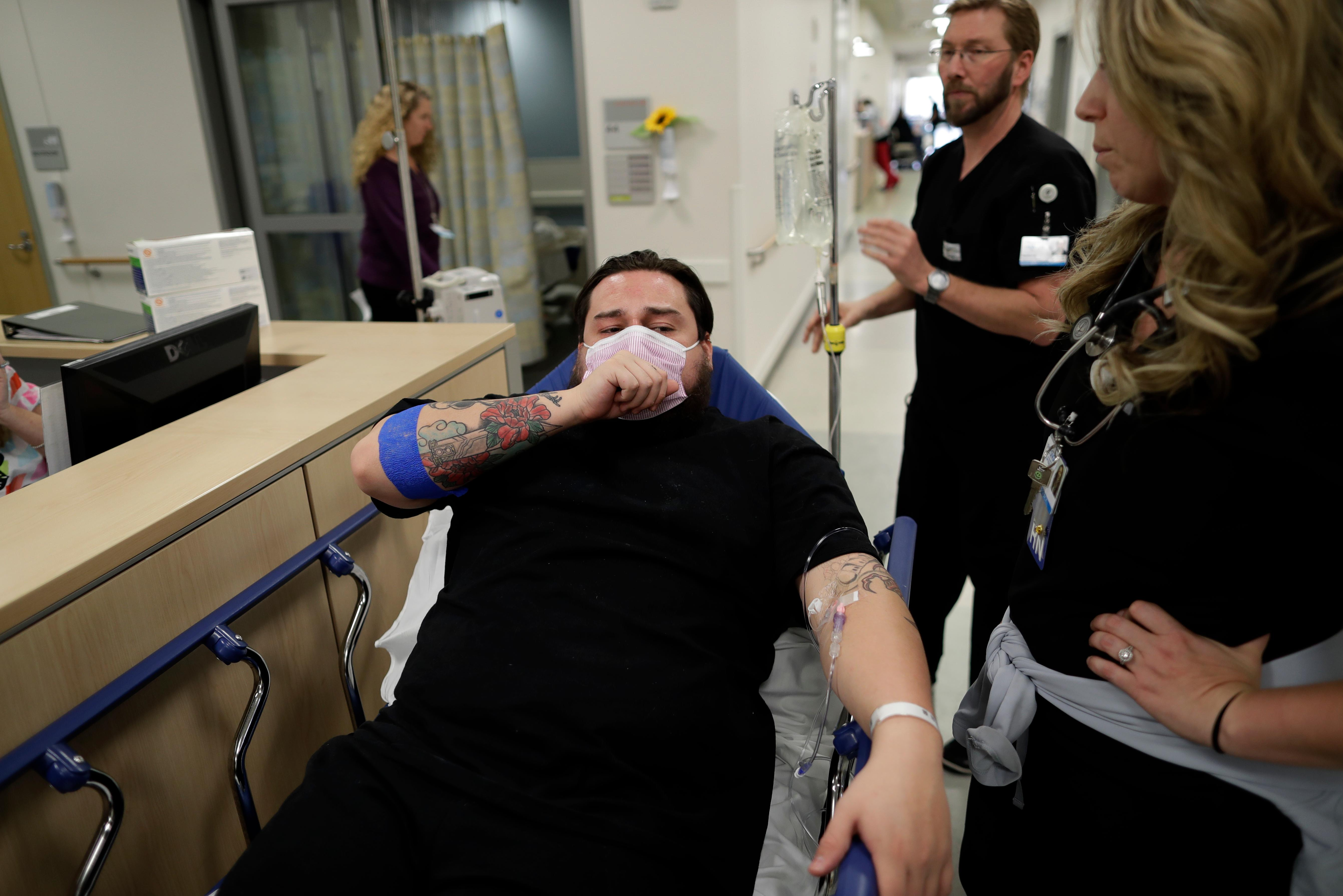 In this Jan. 10, 2017 image, Donnie Cardenas recovers from the flu at the Palomar Medical Center in Escondido, Calif., on Wednesday, Jan. 10, 2018. The San Diego County resident said he was battling a heavy cough for days before a spike his temperature sent him into the emergency room. (AP Photo/Gregory Bull)