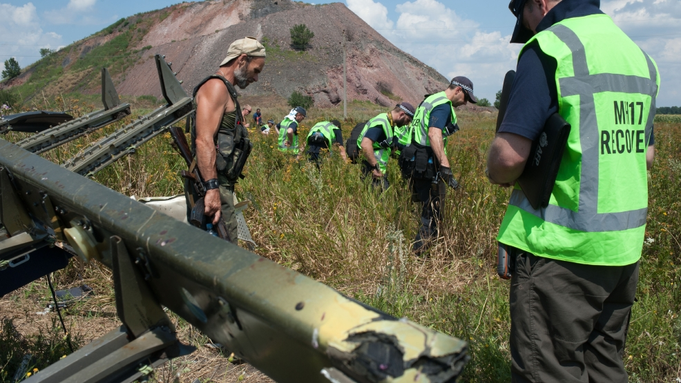 A pro-Russian rebel, left, guards as Australian, Malaysian and Dutch investigators examine the area of the downed Malaysia Airlines Flight 17, near the village of Rossipne, Donetsk region, eastern Ukraine, Tuesday, Aug. 5, 2014. The West has accused Russia of most likely providing the insurgents with surface-to-air missiles that may have been used to shoot down the Malaysia Airlines passenger jet over rebel-held territory on July 17, killing all 298 people on board. (AP Photo)