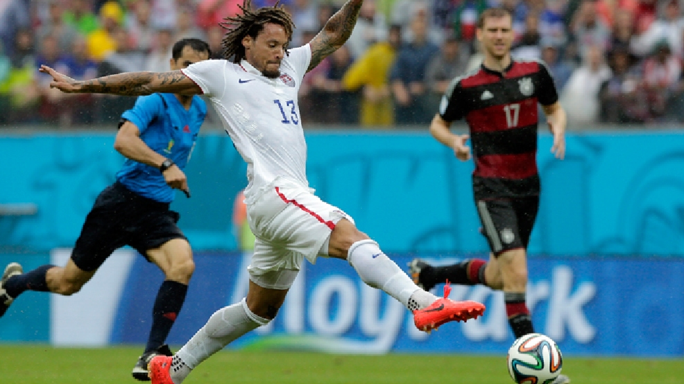United States' Jermaine Jones goes with the ball as Germany's Per Mertesacker watches, at right, during the group G World Cup soccer match between the USA and Germany at the Arena Pernambuco in Recife, Brazil, Thursday, June 26, 2014. (AP Photo/Matthias Schrader)