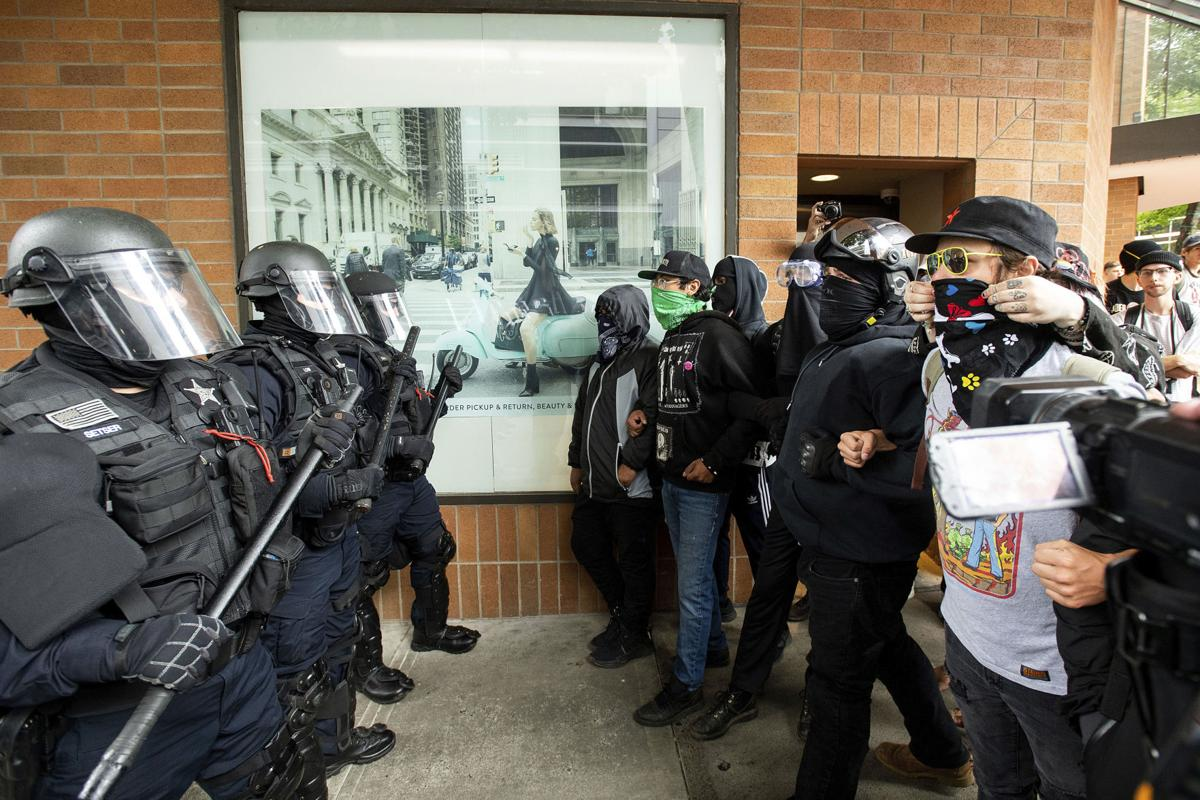 "Police officers face off against protesters opposed to right-wing demonstrators following an ""End Domestic Terrorism"" rally in Portland, Ore., on Saturday, Aug. 17, 2019. Although the main protest remained largely peaceful, some skirmishes erupted in the following hours and police detained multiple protesters. (AP Photo/Noah Berger)<p><br></p>"