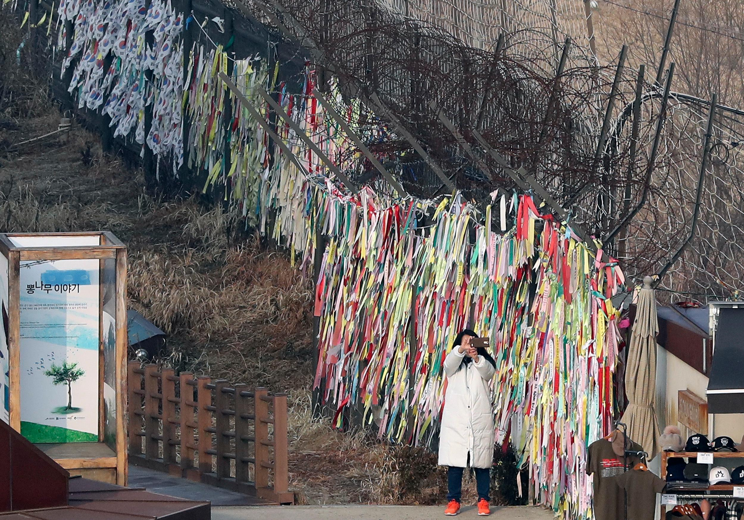 A visitor takes a selfie near the wire fence decorated with ribbons carrying messages to wish for the reunification of the two Koreas at the Imjingak Pavilion in Paju, South Korea, Wednesday, Jan. 17, 2018. The two Koreas are meeting Wednesday for the third time in about 10 days to continue their discussions on Olympics cooperation, days ahead of talks with the IOC on North Korean participation in the upcoming Winter Games in the South. (AP Photo/Lee Jin-man)