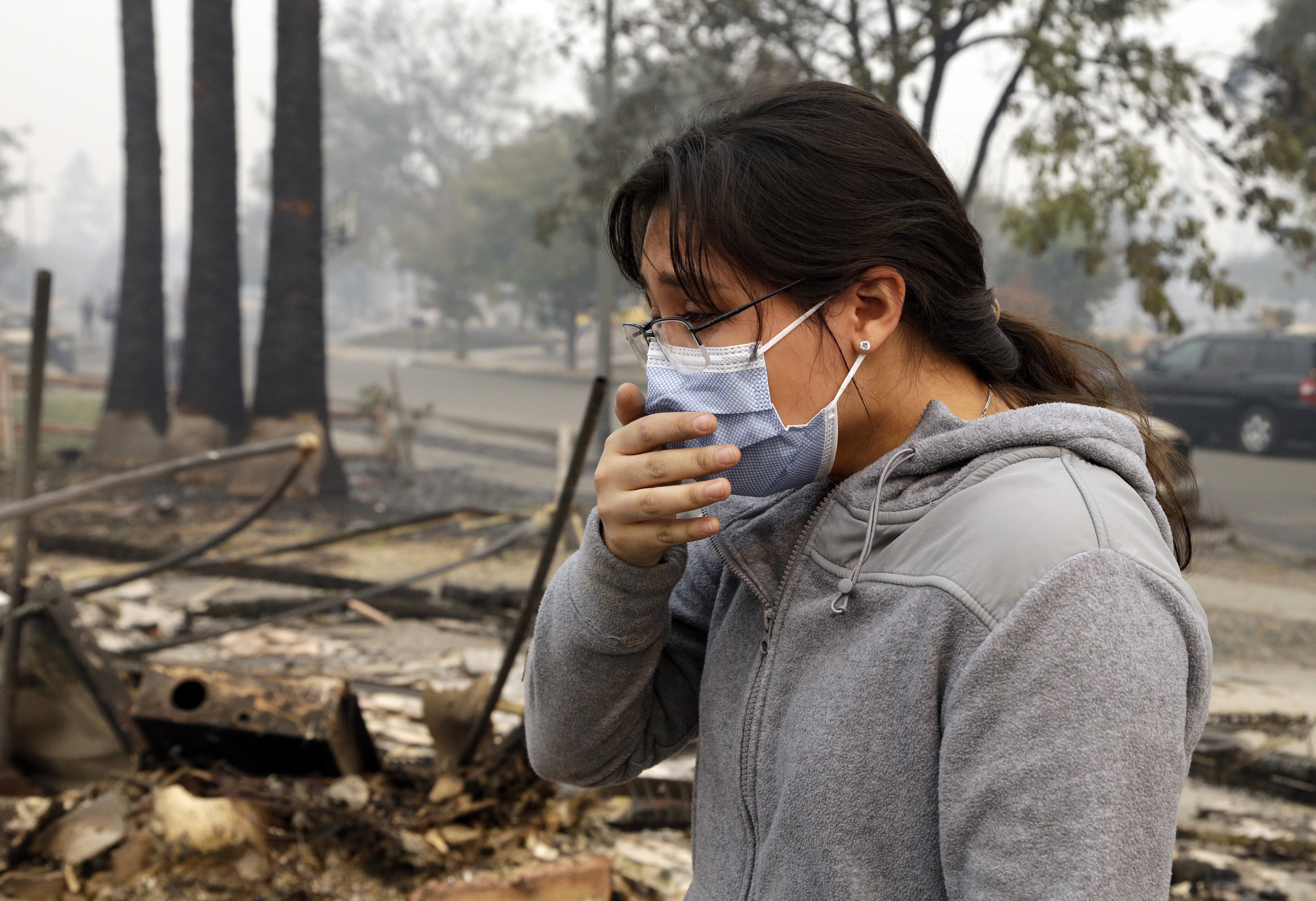 "FILE - In this Oct. 10, 2017, file photo, Leslie Garnica cries while recalling the fire which destroyed her family home in the Coffey Park area of Santa Rosa, Calif. Garnica, a 17-year-old high school senior who was born and raised in Coffey Park, liked to open her blinds and window so she could see the three palm trees in her front yard as she laid in bed and listened to music. ""This is all I've ever known, and it's kind of weird knowing that you have to start again, find something new,"" Garnica said. ""This is what I'm used to. But I don't have it anymore."" (AP Photo/Ben Margot, File)"