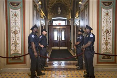 U.S. Capitol Police officers stand guard as doors are locked down inside the Capitol Building during the shooting at the Washington Navy Yard, Monday, Sept. 16, 2013, in Washington.