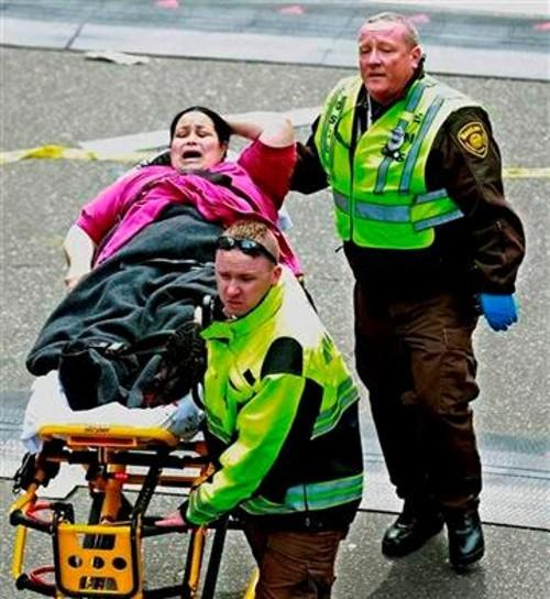 Medical workers aid an injured woman at the finish line of the 2013 Boston Marathon following two explosions there, Monday, April 15, 2013 in Boston.