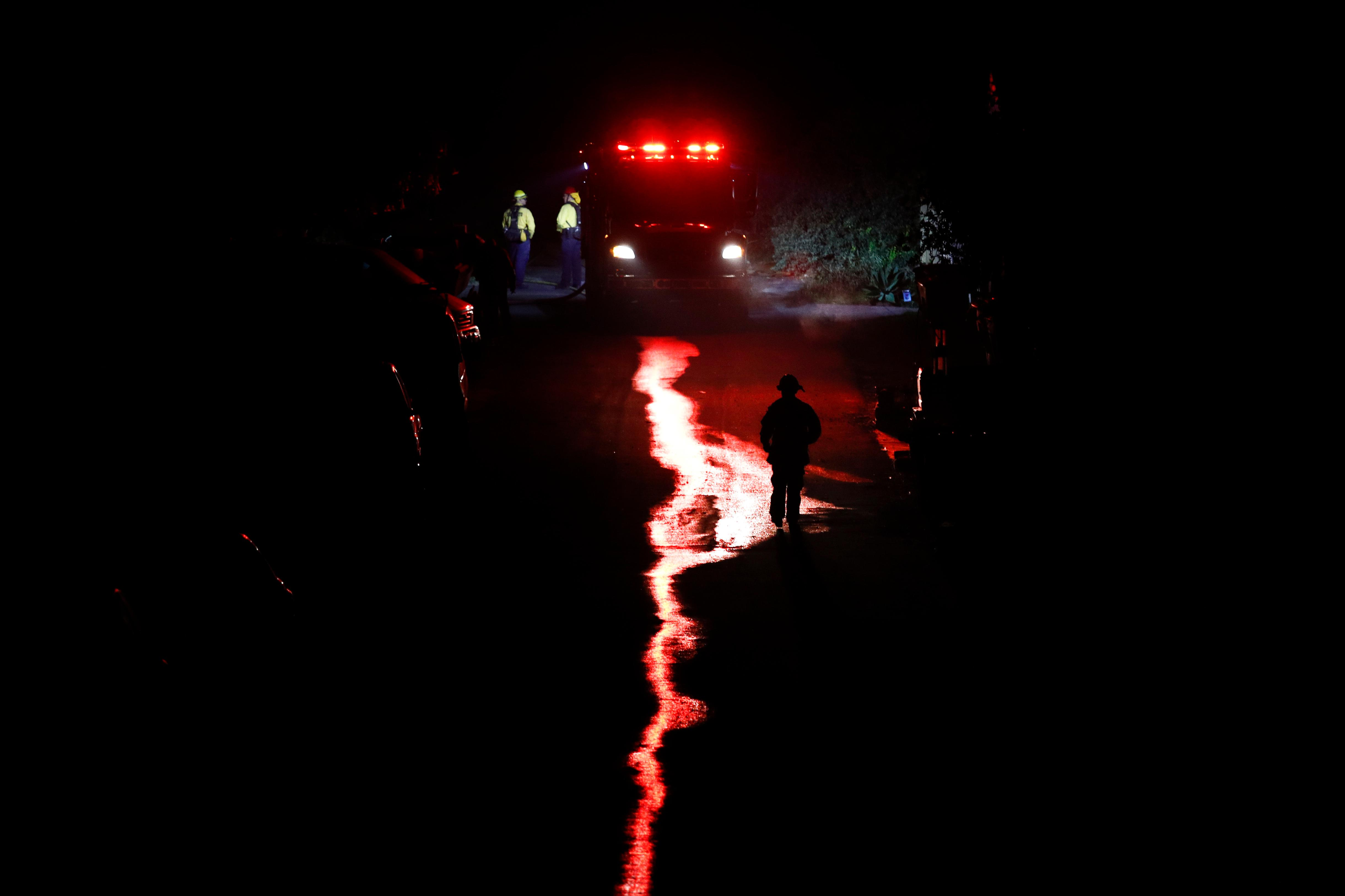 A firefighter walks along an alley toward a firetruck as a wildfire burns along a hillside near homes in La Conchita, Calif., Thursday, Dec. 7, 2017. The wind-swept blazes have forced tens of thousands of evacuations and destroyed dozens of homes. (AP Photo/Jae C. Hong)