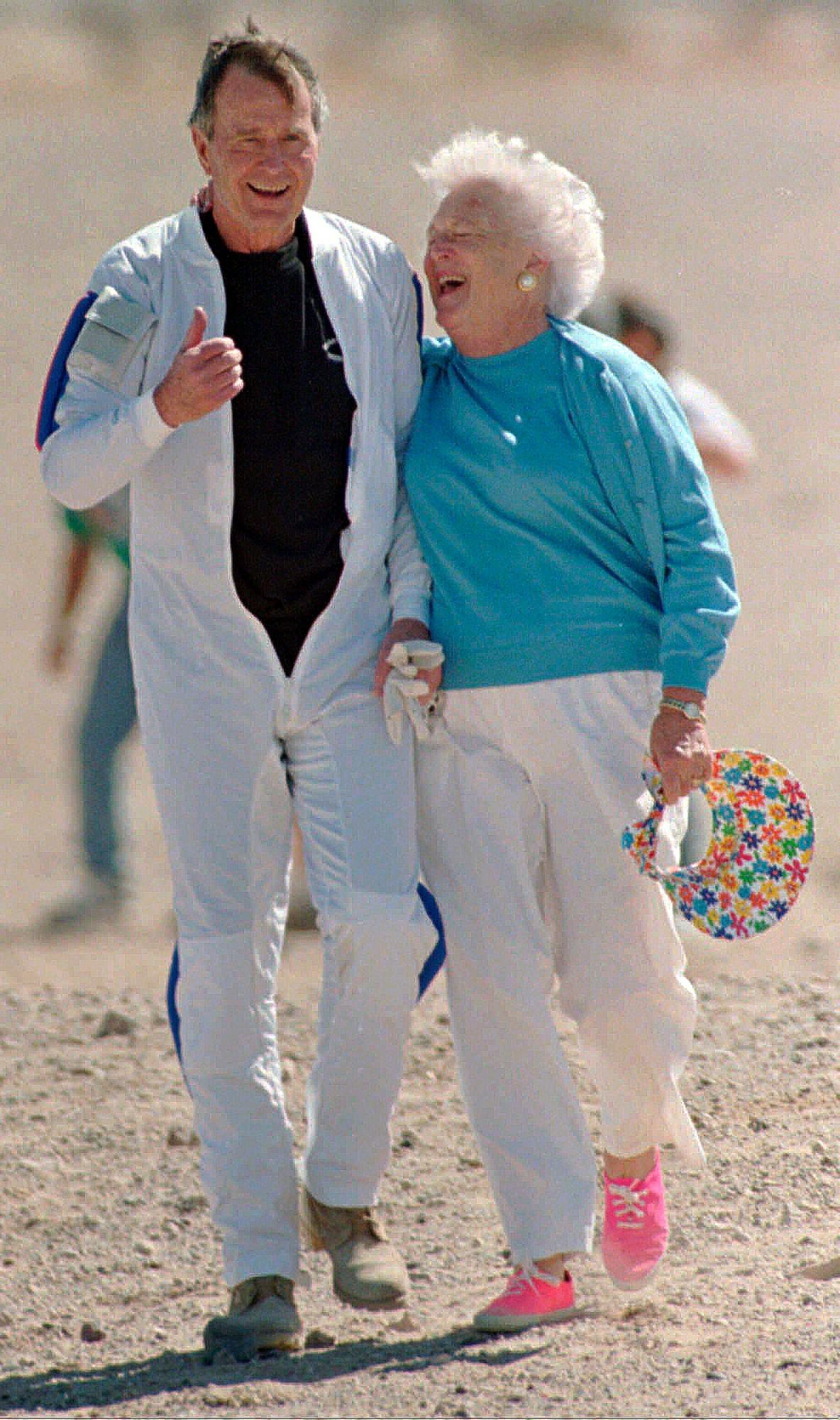 "FILE - In this March 25, 1997, file photo, former President George H.W. Bush gets a hug from his wife Barbara after he made a successful parachute jump at the U.S. Army's Yuma Proving Ground outside of Yuma, Ariz. Former first couple George and Barbara Bush's relationship is a true love story, described by granddaughter Jenna Bush Hager as ""remarkable."" They met at a Christmas dance. She was 17. He was 18. Two years later they were married. Now 73 years later, with Barbara Bush declining further medical care for health problems, they are the longest-married couple in presidential history. (AP Photo/Mike Nelson, Pool, File)"